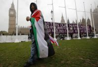 A pro-Palestine supporter wears a Palestinian and Union flag outside the Houses of Parliament in London