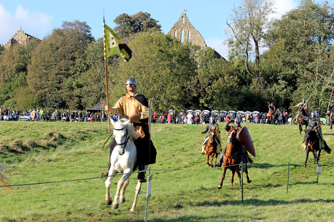 Norman knights carrying banners representing the Dukes of Normandy ride down the field during the re-enactment