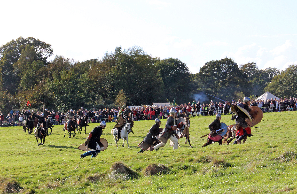 Norman troops and knights race towards the Anglo-Saxons in a dramatic re-enactment of the battle