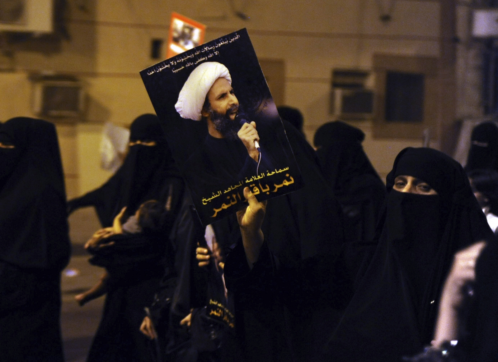 A protester holds up a picture of Sheikh Nimr al-Nimr during a rally at the coastal town of Qatif, against Sheikh Nimr's arrest