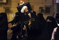A protester holds up a picture of Sheikh Nimr al-Nimr during a rally at the coastal town of Qatif, against Sheikh Nimr\'s arrest