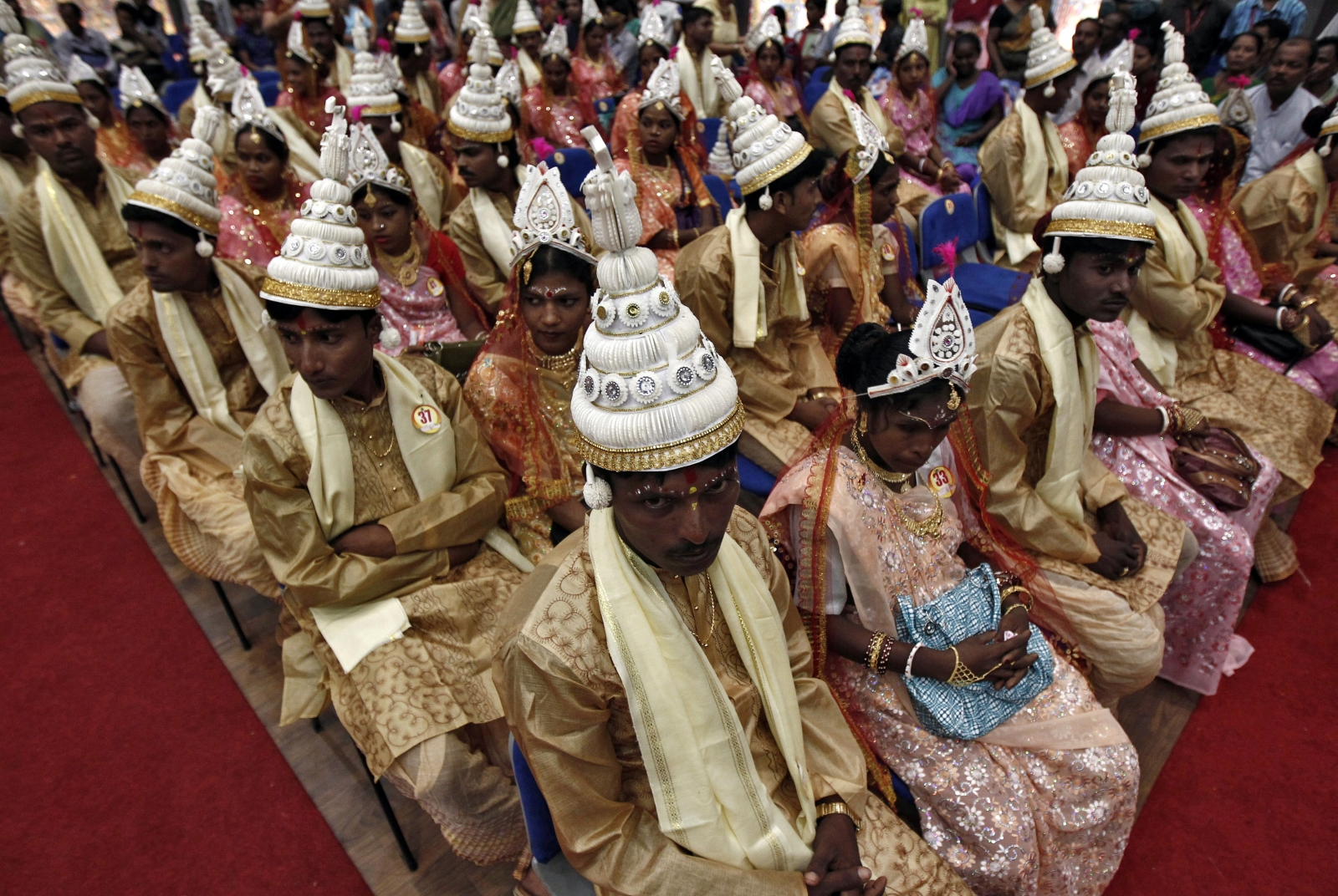 Brides and grooms sit before the start of a mass marriage ceremony in Kolkata June 18, 2014.