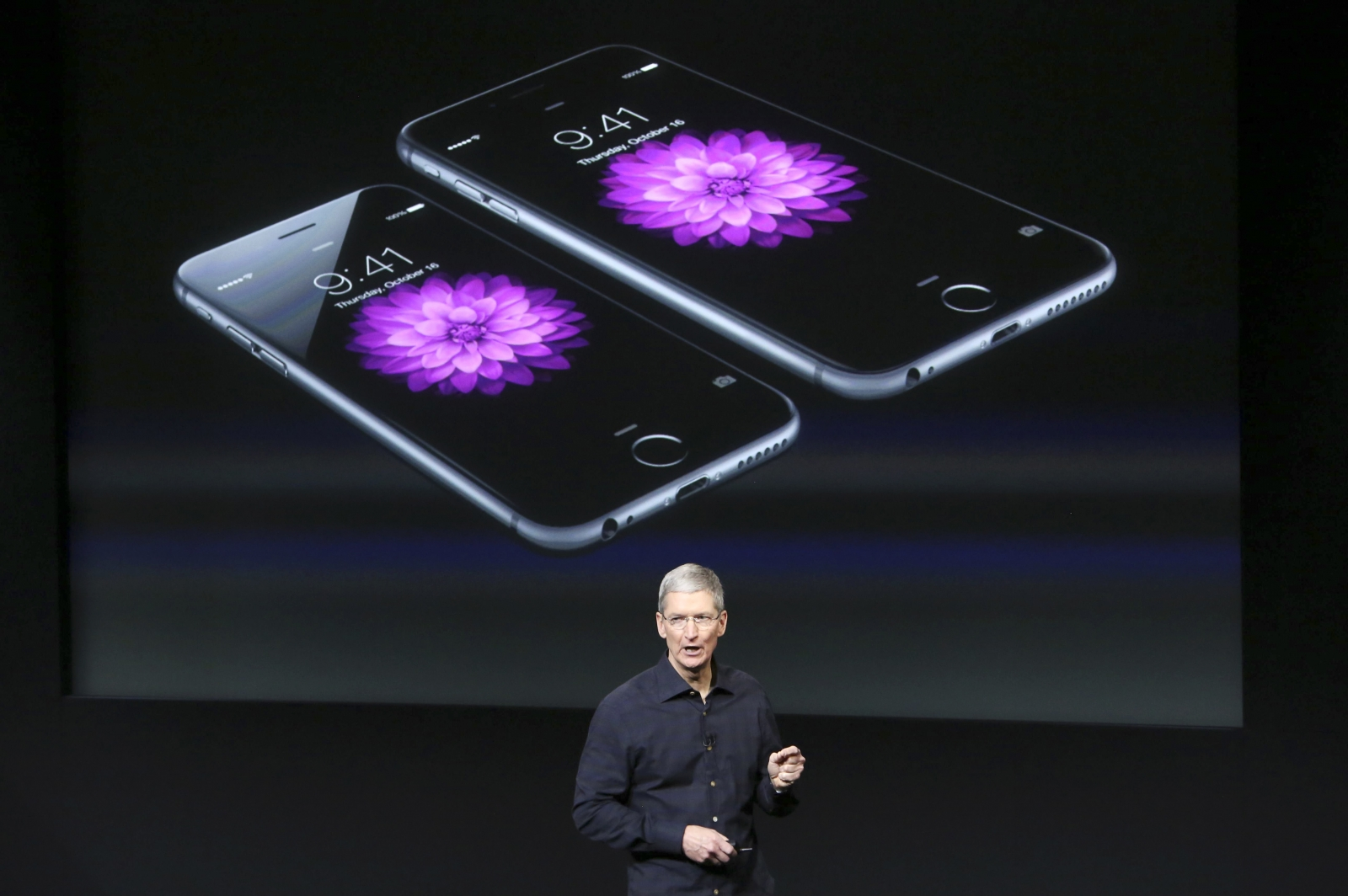 Apple CEO Tim Cook stands in front of a screen displaying the IPhone 6 during a presentation at Apple headquarters in Cupertino, California October 16, 2014