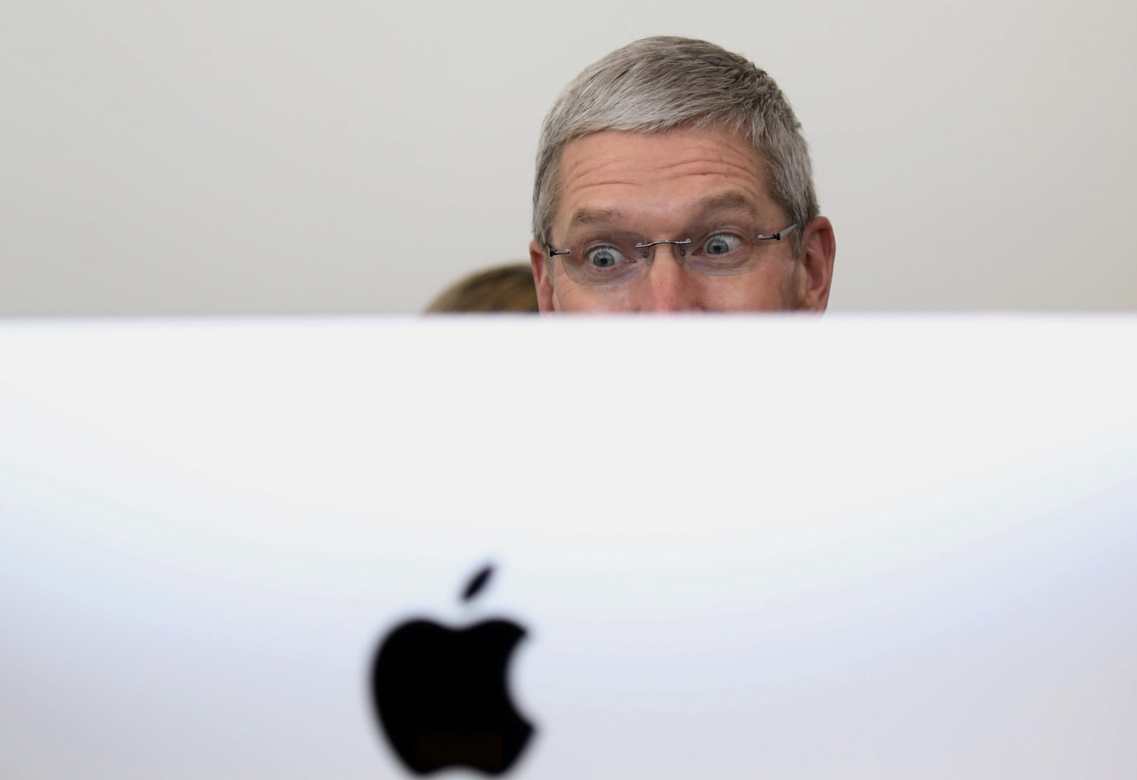 Apple CEO Tim Cook looks at a new IMac after a presentation at Apple headquarters in Cupertino, California October 16, 2014