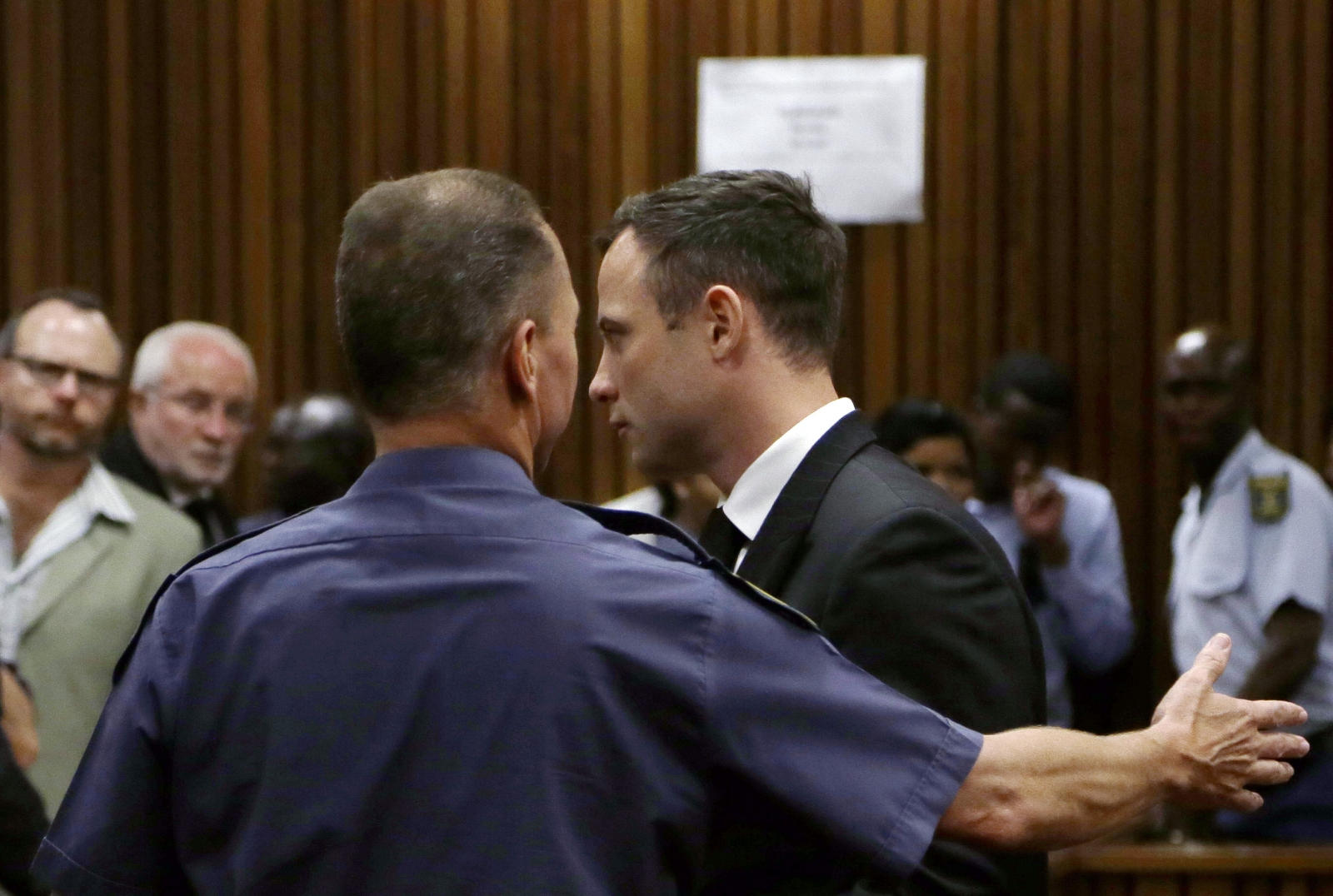 Oscar Pistorius led away to a cell by  a court guard after he was jailed for five years