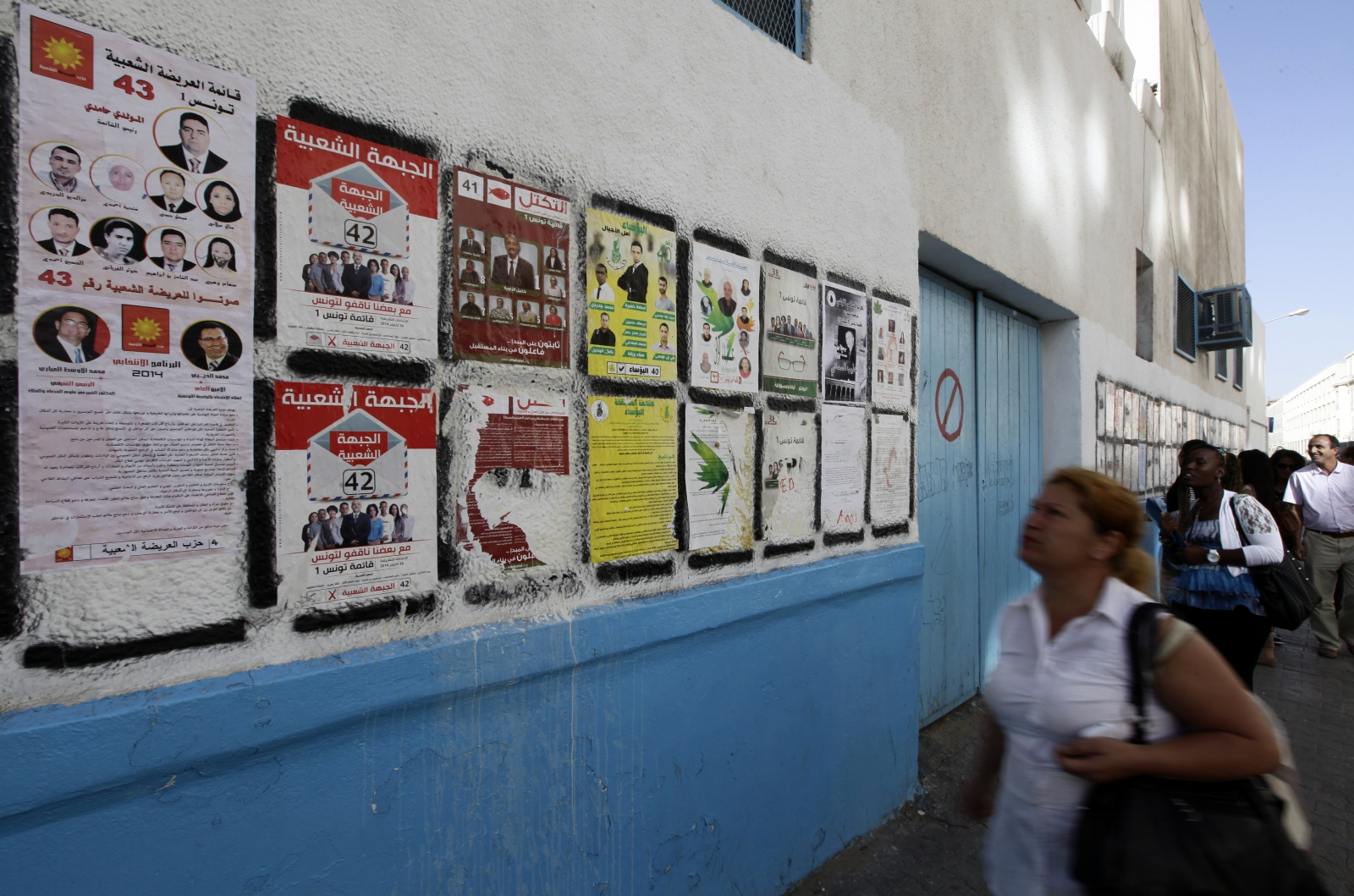 People look at parliamentary election posters in Tunis