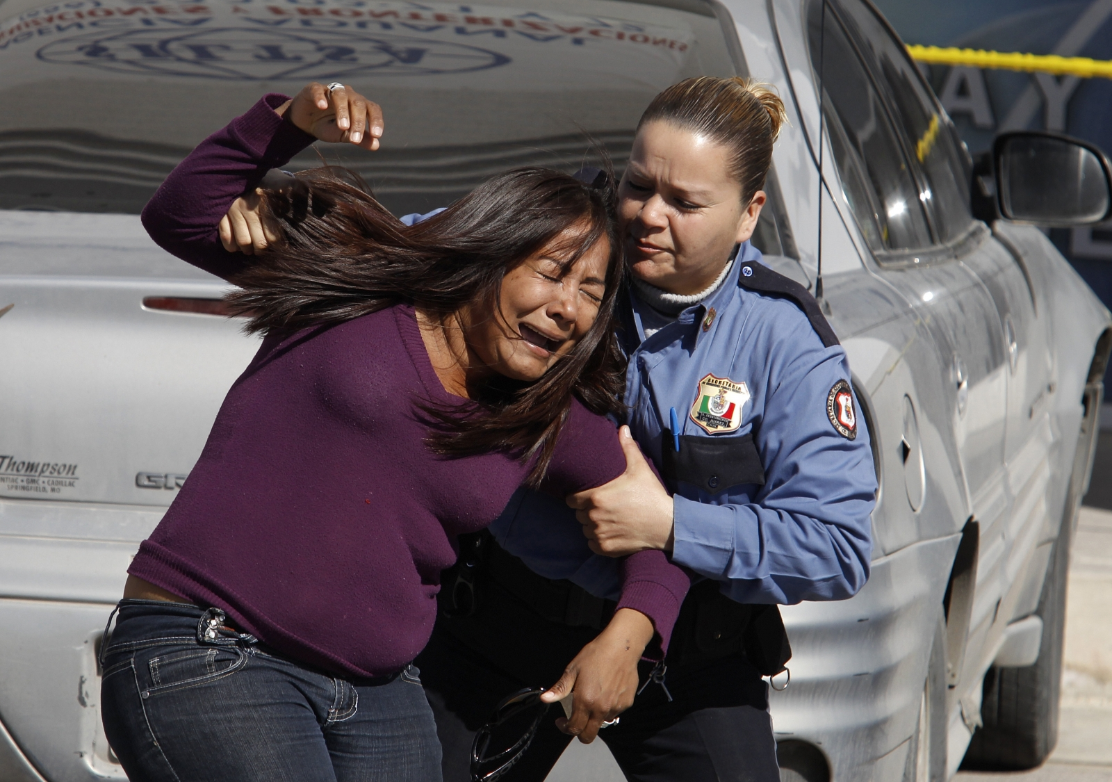 A woman, whose sister is believed to have been killed by a Mexican drugs cartel, is comforted by a police office in Ciudad Juarez, Mexico. (Reuters)