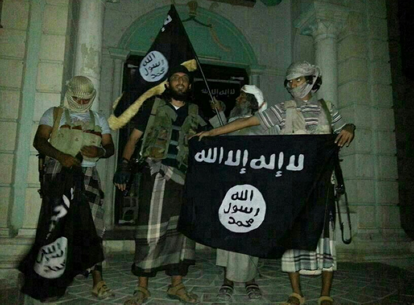 Yemeni al Qaida militants pose with the black flag of jihad, since adopted by Isis (Getty)