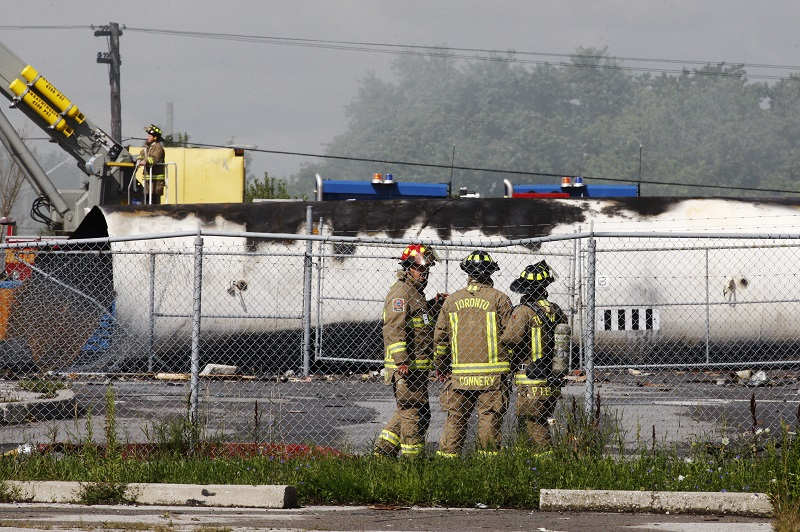 Canadian firefighters stand in front of an exploded propane tank