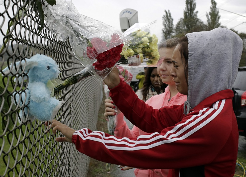 Student Tyanna Davis places flowers outside Marysville-Pilchuck High School the day after Jaylen Fryberg went on a shooting spree in the school cafeteria