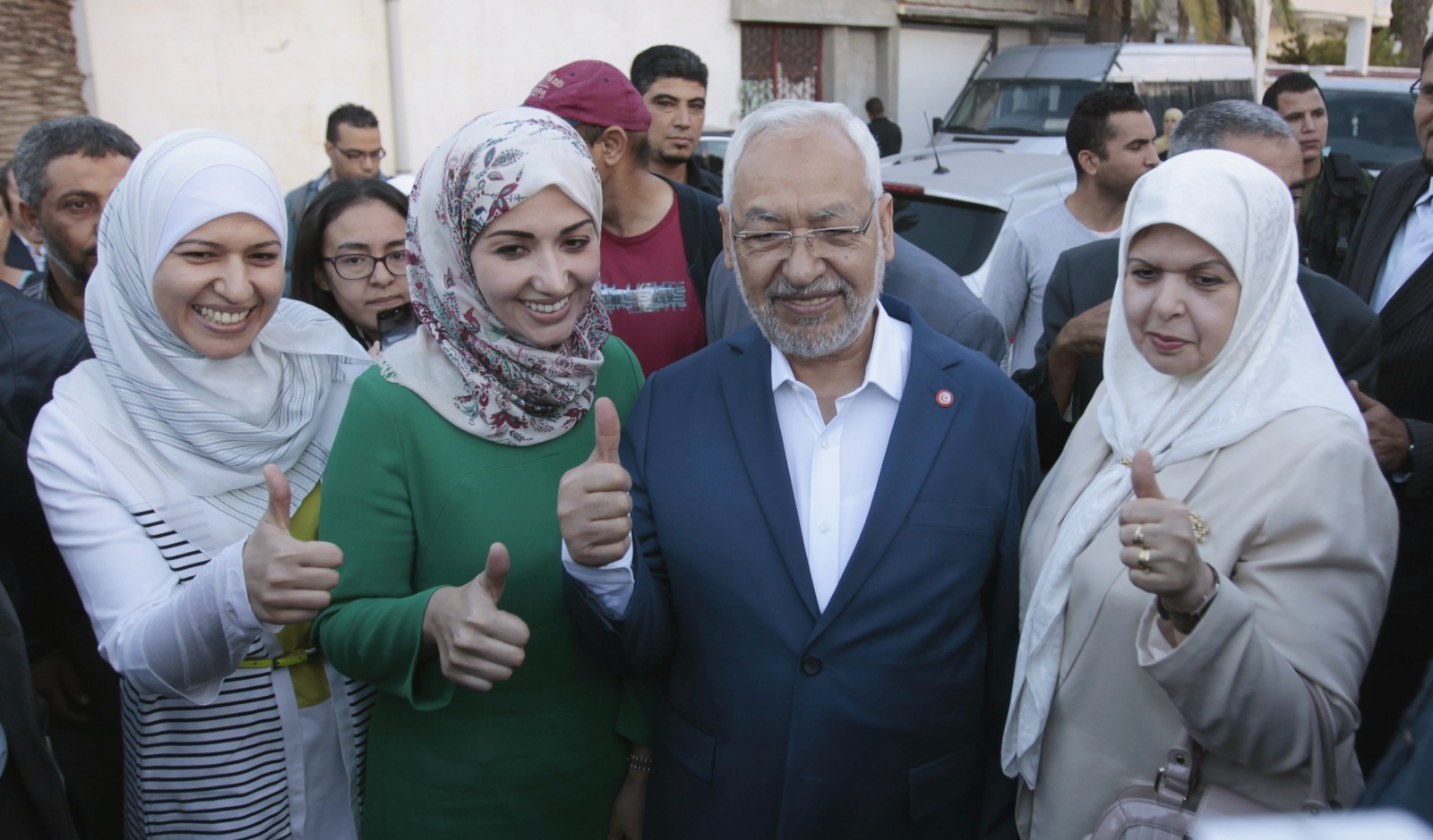 Rached Ghannouchi (C), leader of the Tunisian Islamist party Ennahda, gestures with his wife and two daughters Yousra (L) and Soumaya (2nd L) at a polling station during an election in Tunisia