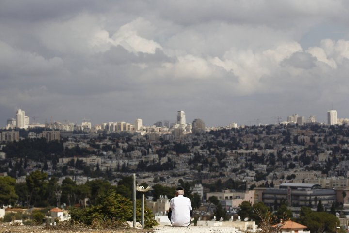 A view of Jerusalem is seen in the background as a man sits in Giv'at HaMato