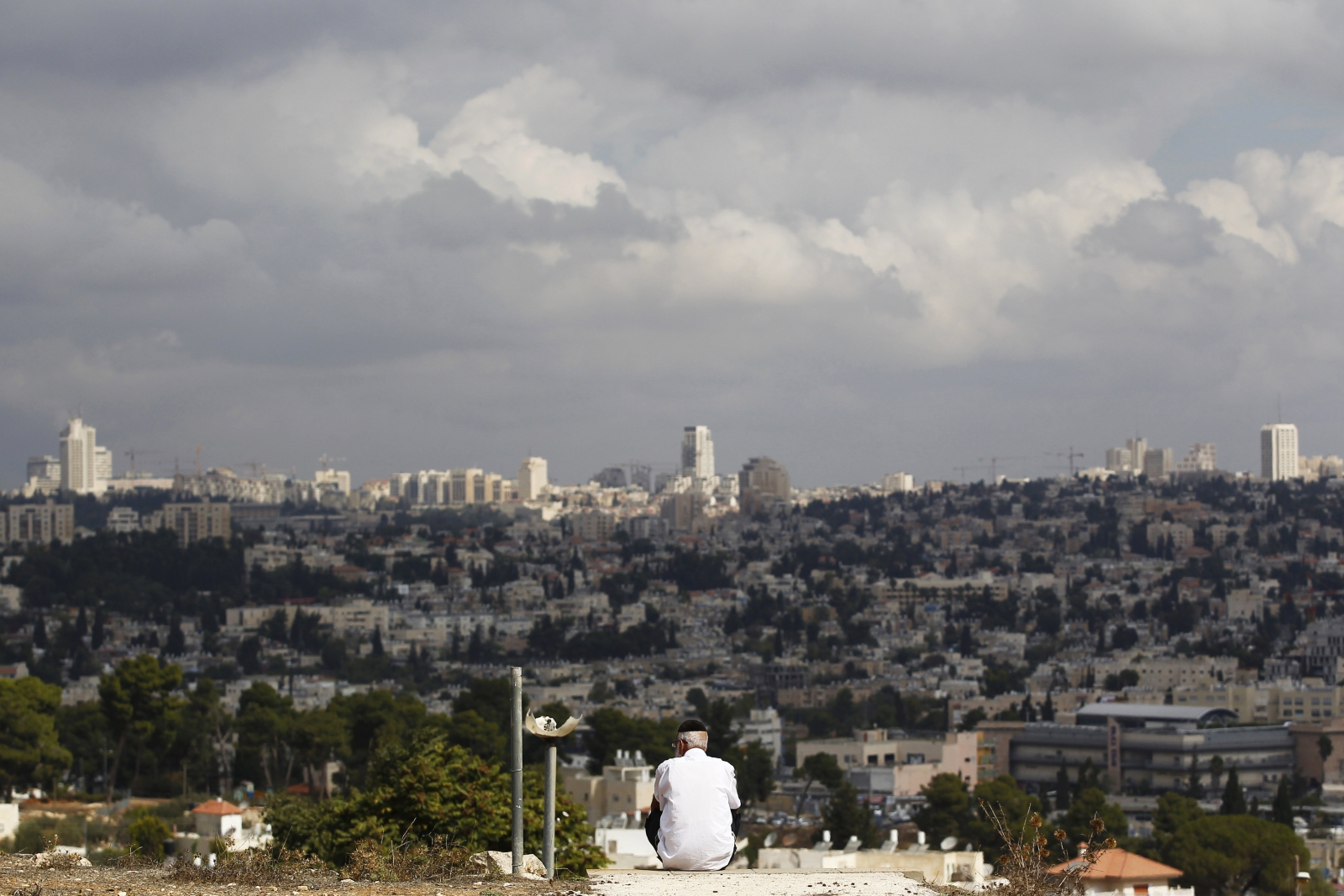 A view of Jerusalem is seen in the background as a man sits in Givat HaMato