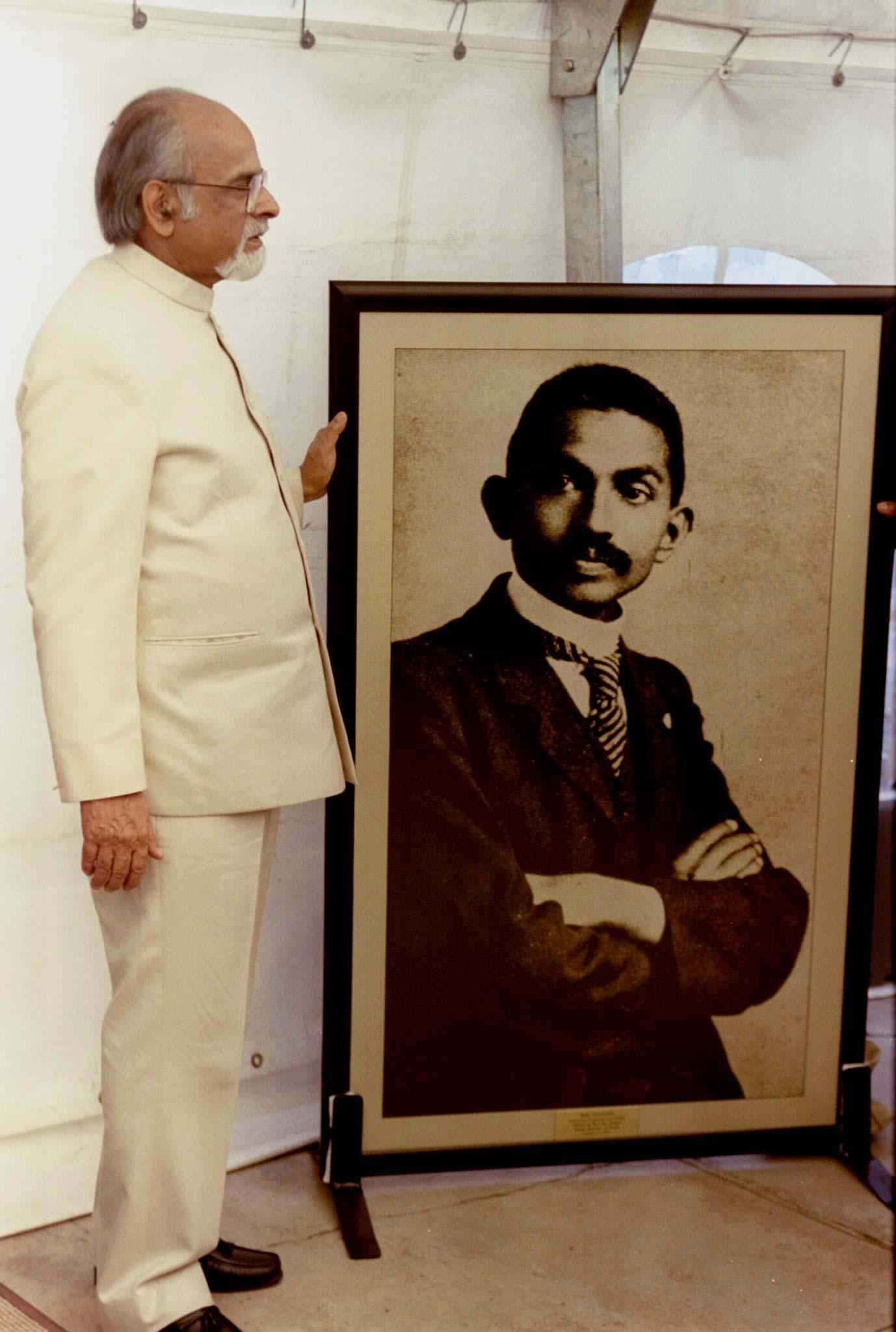 Indian Prime Minister Inder Kumar stands next to a picture of Mahatma Gandhi at the Johannesburg prison