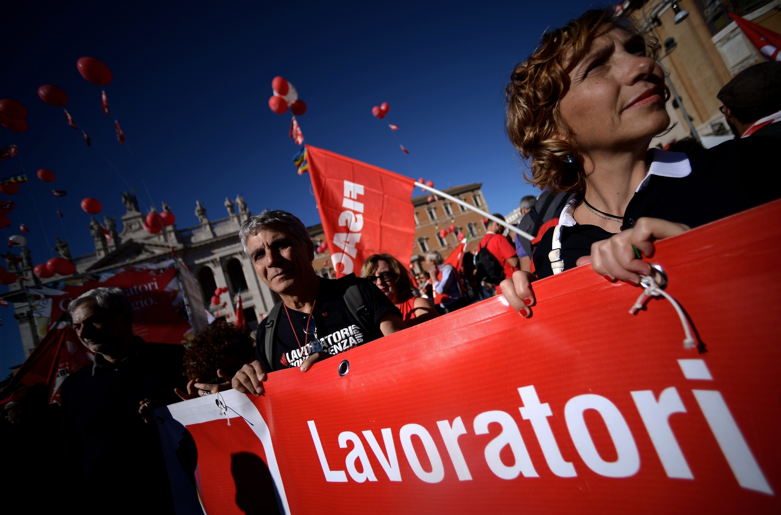 Protestors holding a banner arrive in San Giovanni square during a demonstration organised by Italian General Confederation of Labour (CGIL) union