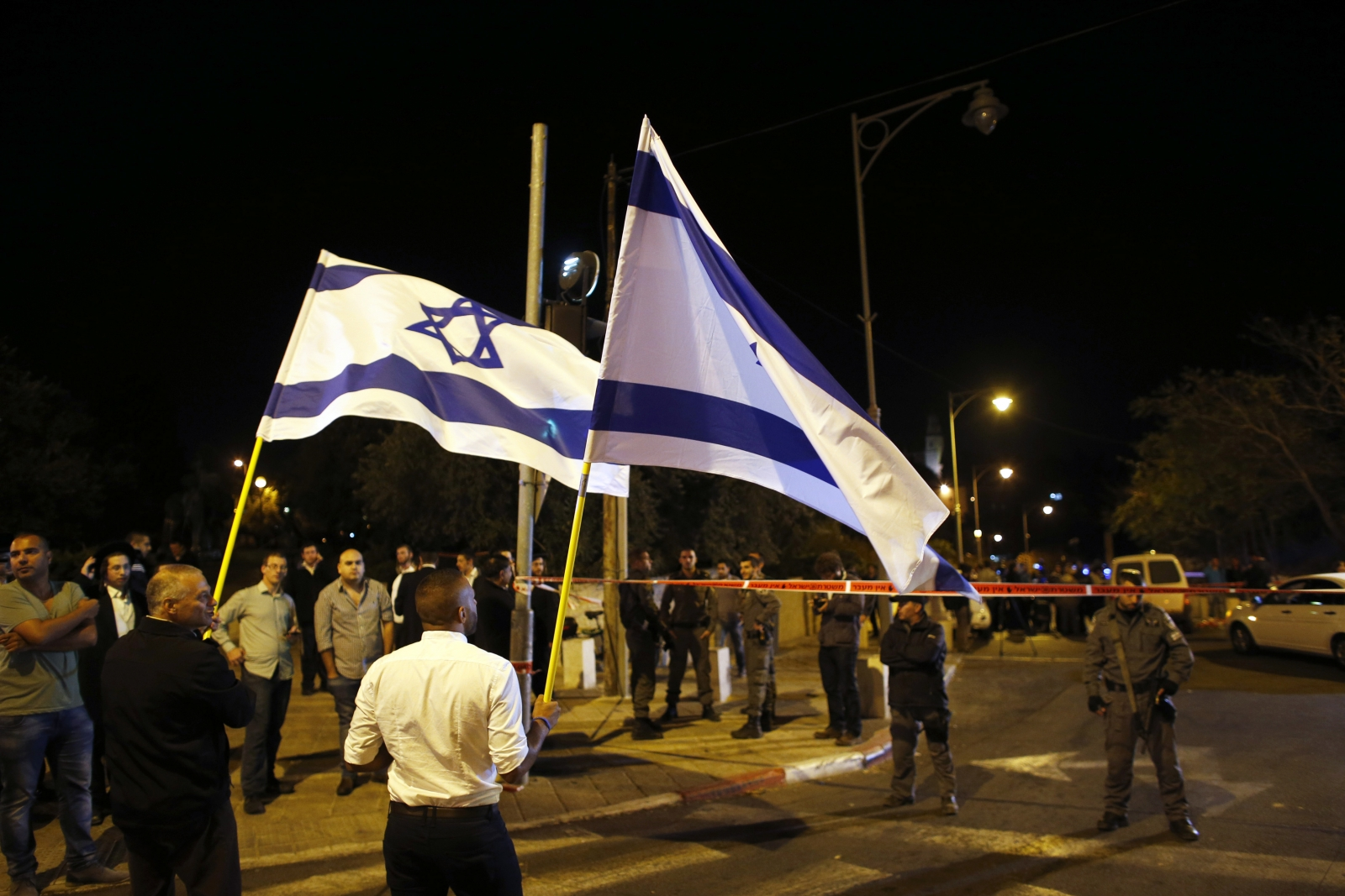 Israelis wave national flags next to security personnel securing an area in Jerusalem where a far-right activist was shot and wounded,