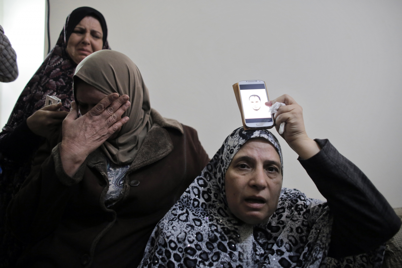 The mother of Palestinian Moataz Hejazi (R) holds a picture of him over a phone over her head at the family house in the Abu Tor neighbourhood of east Jerusalem