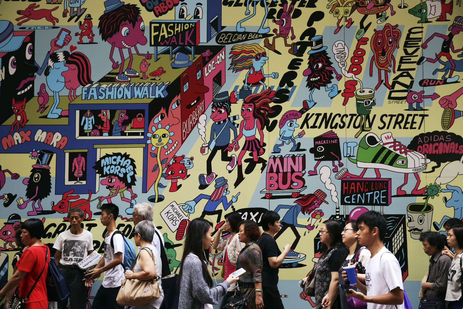 Commuters and shoppers pass by a colourful wall at the Causeway Bay shopping district in Hong Kong