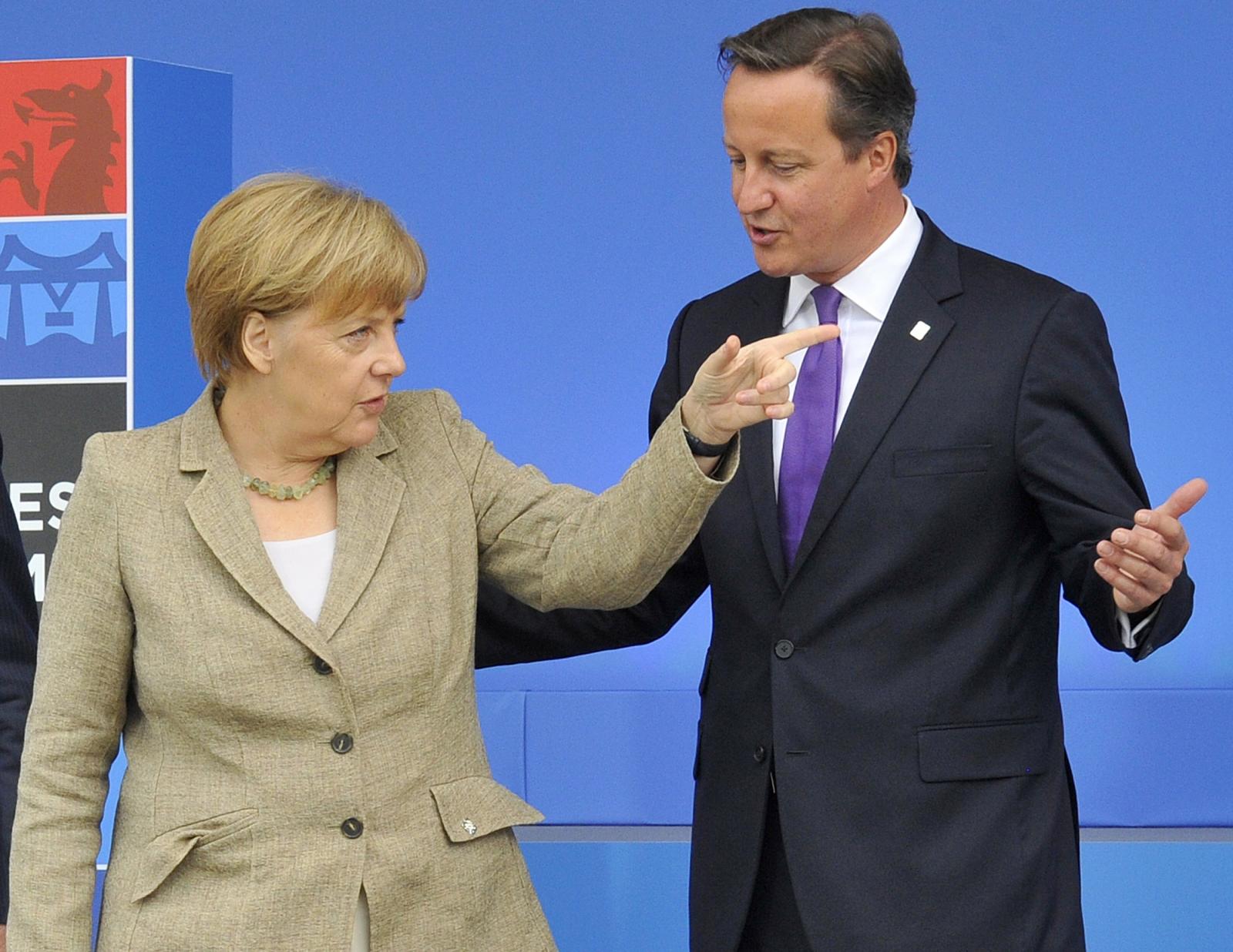 Britain's Prime Minister David Cameron (R) greets German Chancellor Angela Merkel