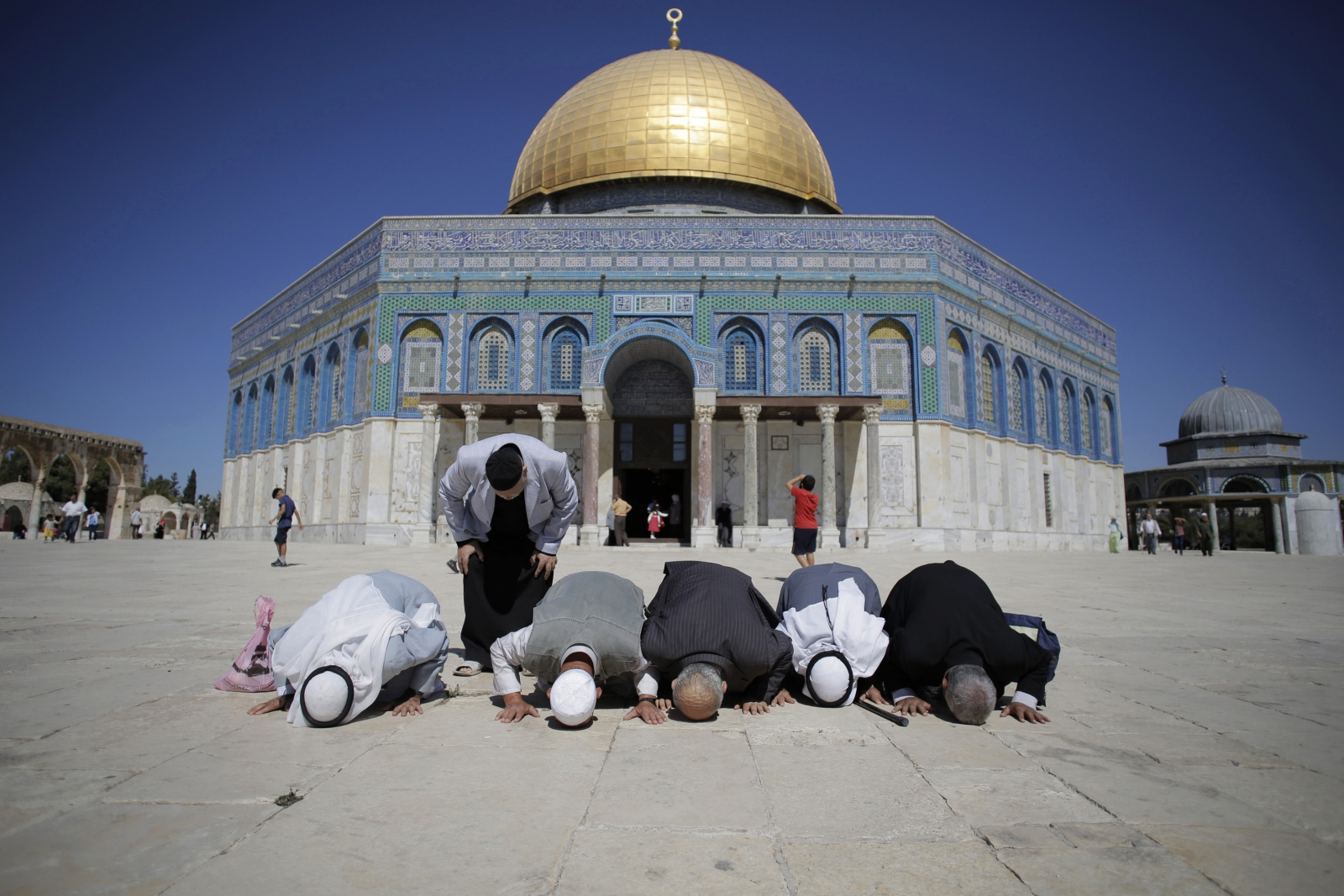 Palestinians from Gaza pray in front of the Dome of the Rock during their visit at the compound known to Muslims as Noble Sanctuary and to Jews as Temple Mount in Jerusalem's Old City October 5, 2014