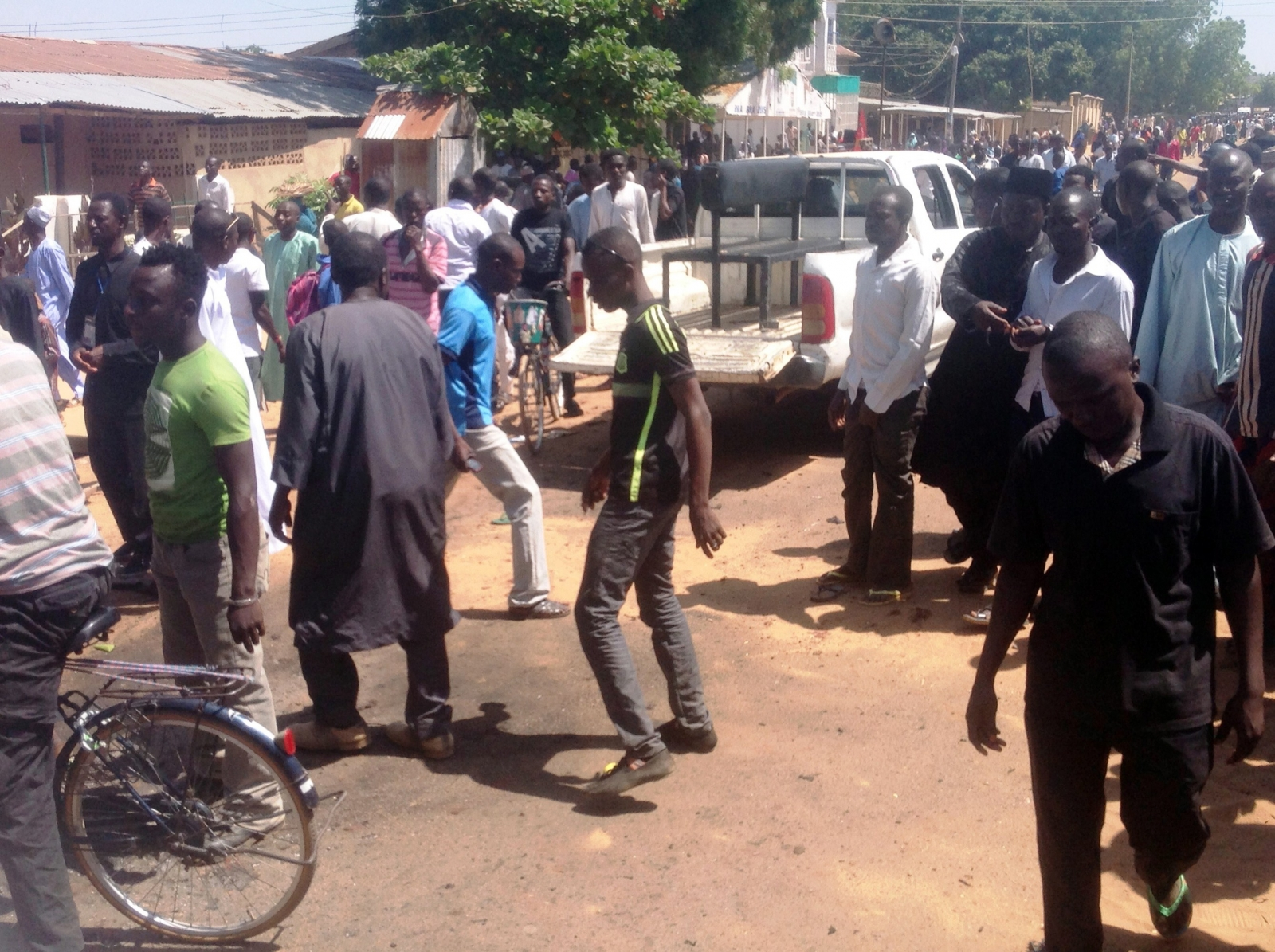 Shiite faithful dressed in black walk at the scene of a suicide blast in the northeast Nigerian town of Potiskum