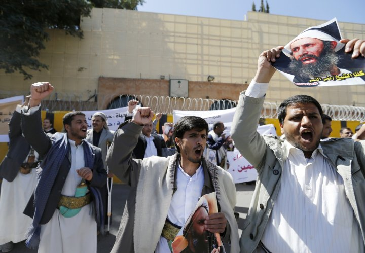 Shi'ite protesters carry posters of Sheikh Nimr al-Nimr during a demonstration outside the Saudi embassy in Sanaa