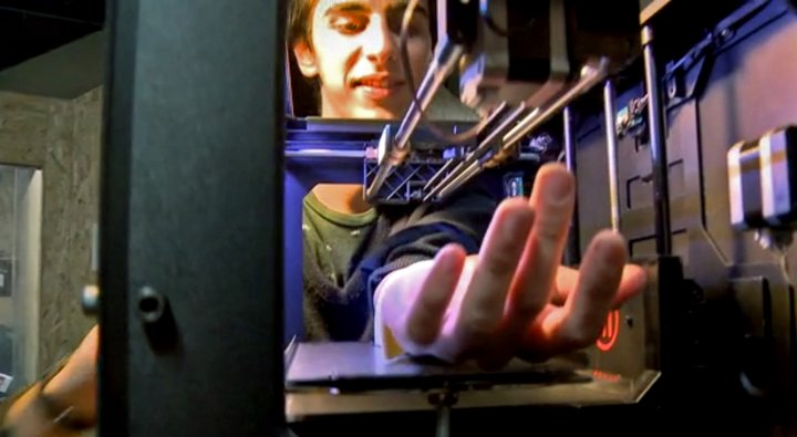 A volunteer places his arm into an automated tattooing machine that has been modified from a MakerBot Replicator 3D printer
