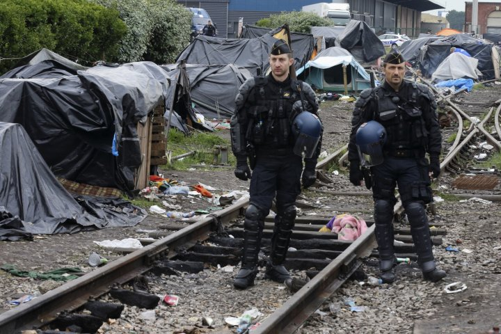 French gendarmes stand guard near makeshift shelters as they evacuated immigrants of an improvised camp in Calais, northern France, May 28, 2014