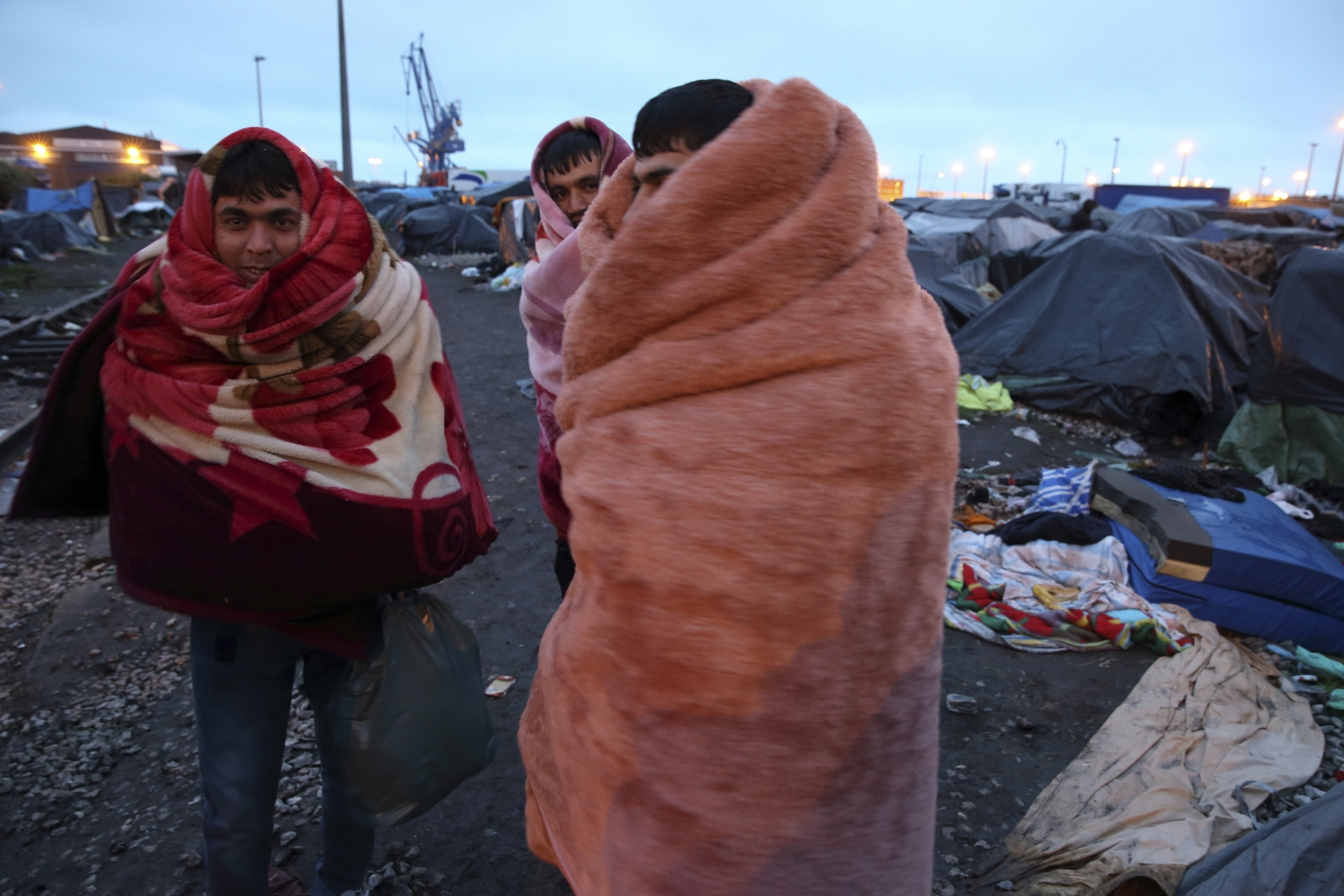 Afghan immigrants use blankets to keep warm near makeshift shelters before French police evacuated them from an improvised camp in Calais, northern France, May 28, 2014.