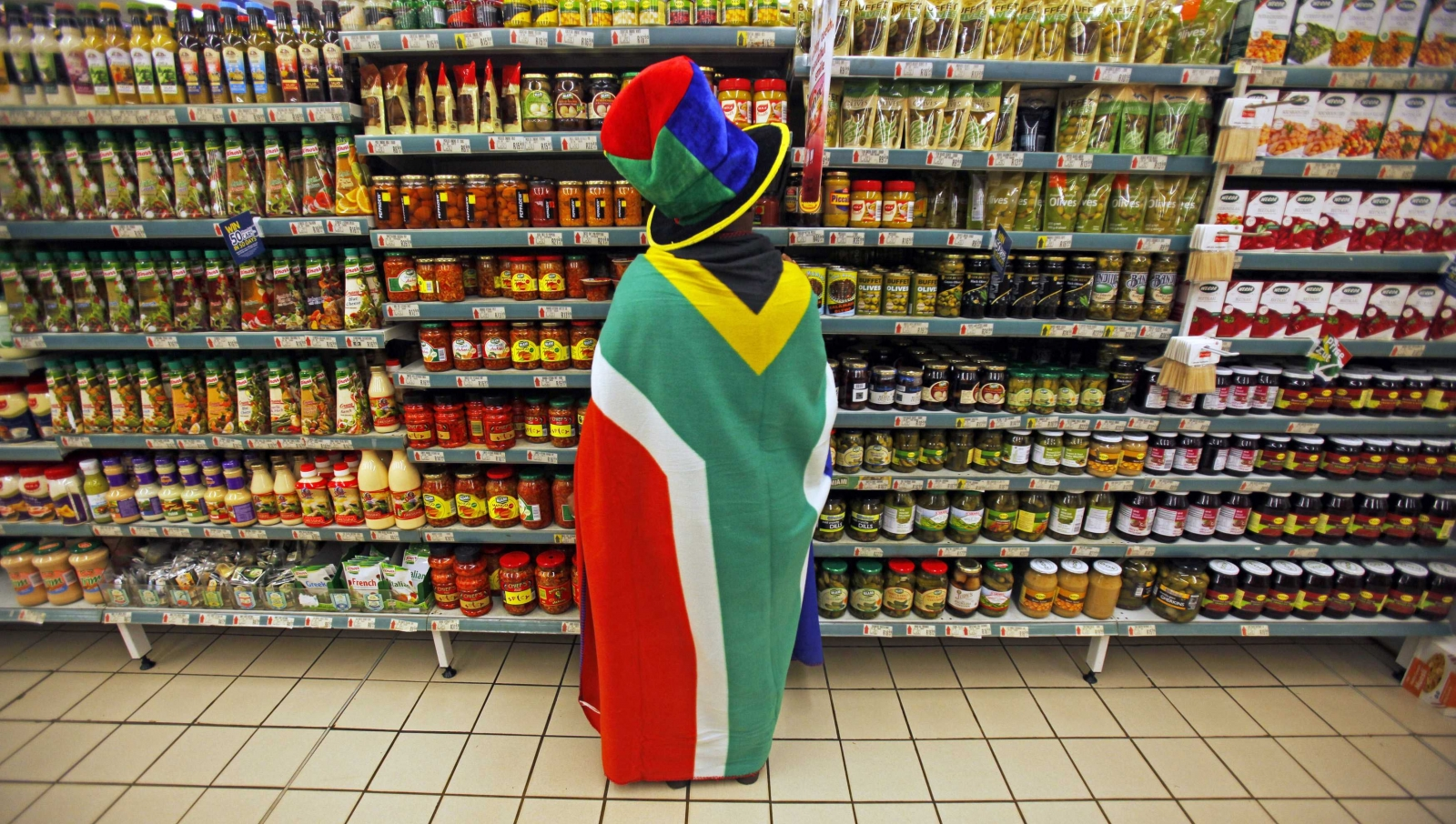 woman with a South African flag draped around her shops for groceries in Pretoria
