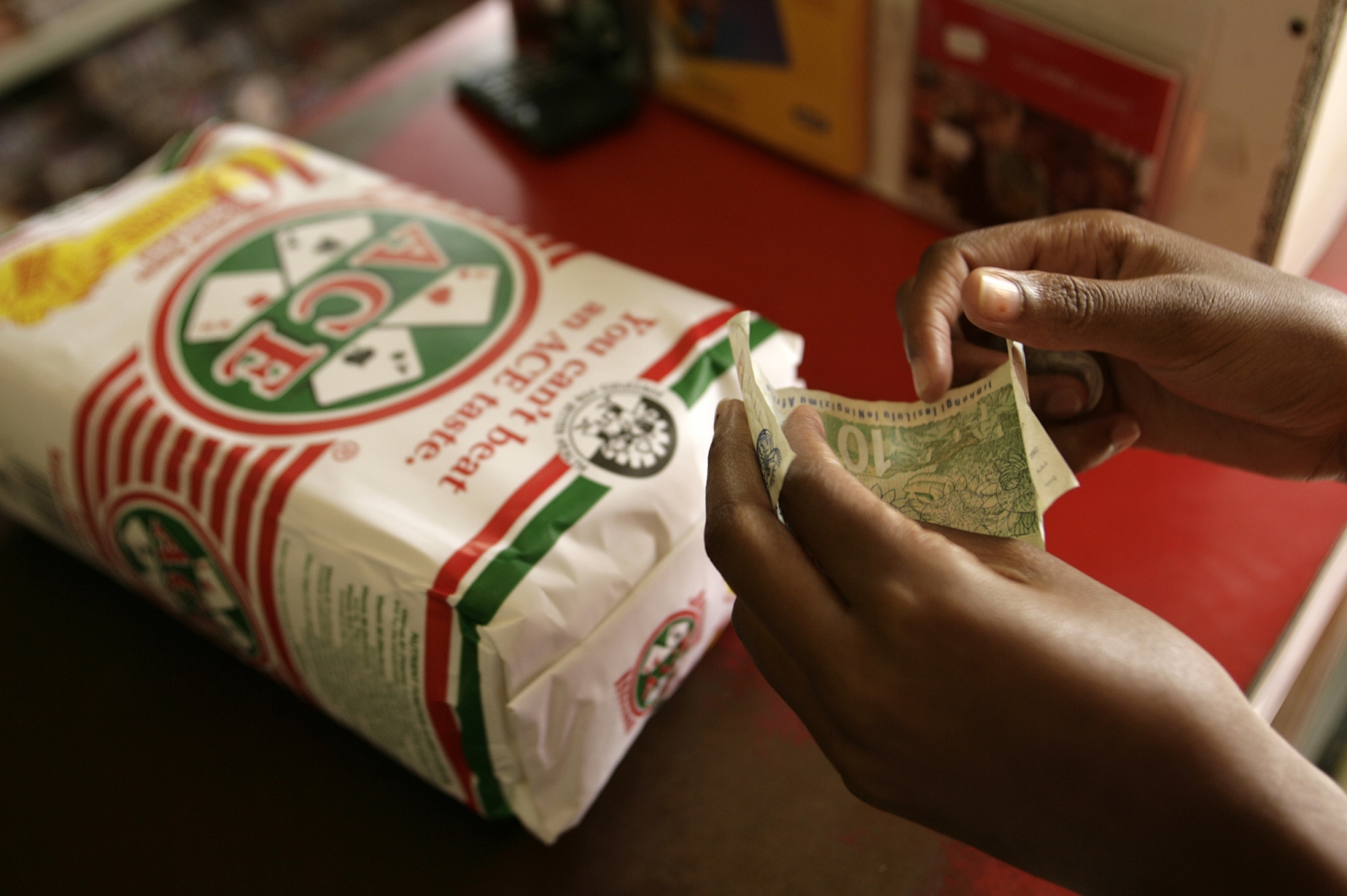 customer prepares to pay for a small bag of maize meal at a shop in Soweto south west of Johannesburg