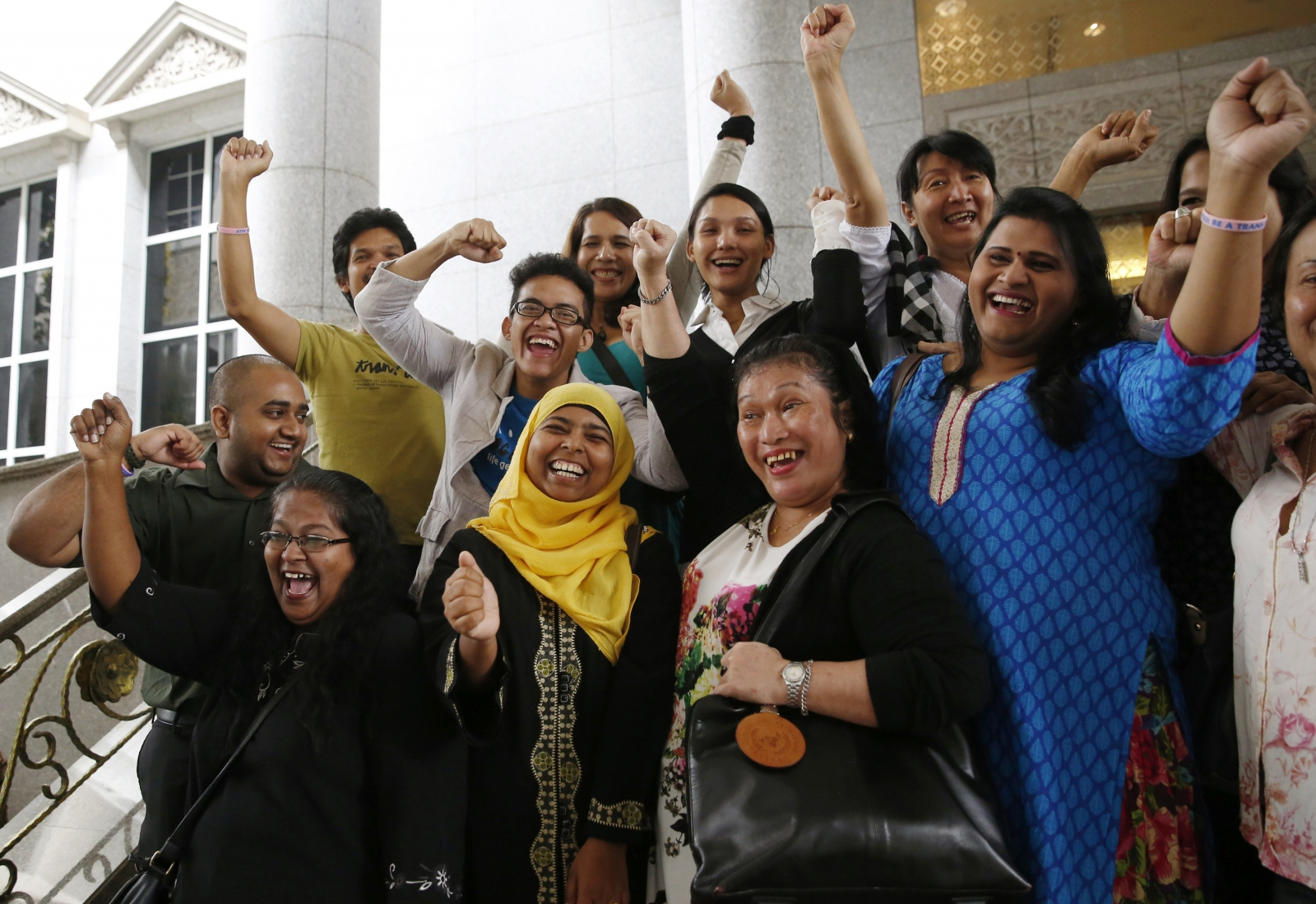 Activists celebrate overturning a sharia law against cross-dressing at the Appeals Court in the Palace of Justice in Putrajaya November 7, 2014