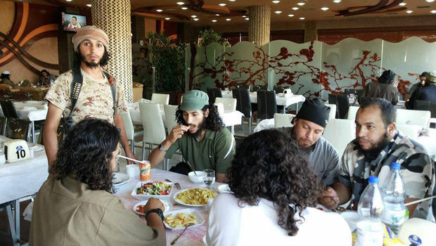 An image from the Syrian Observatory for Human rights, which shows Isis militants enjoying a meal in Raqqa, Syria.