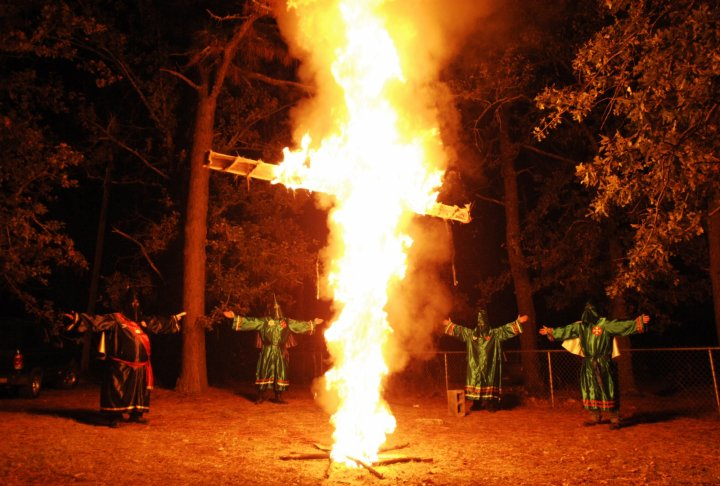 Members of the Ku Klux Klan (KKK) participate in a cross lighting ceremony at a Klansman's home in Warrenville, South Carolina