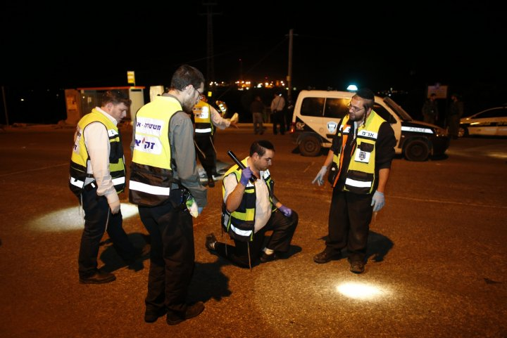 Members of the Israeli Zaka emergency response team survey the scene of a stabbing attack near the West Bank