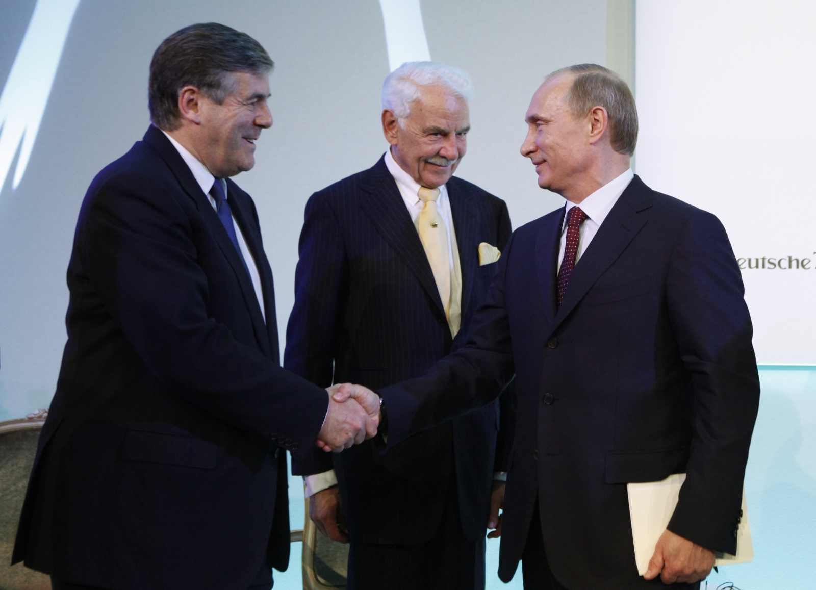 Russian President Vladimir Putin (R) shakes hands with ex-Deutsche Bank Chief Executive Officer Josef Ackermann (L) as the head of Knauf Group Nikolaus Wilhelm Knauf in 2010