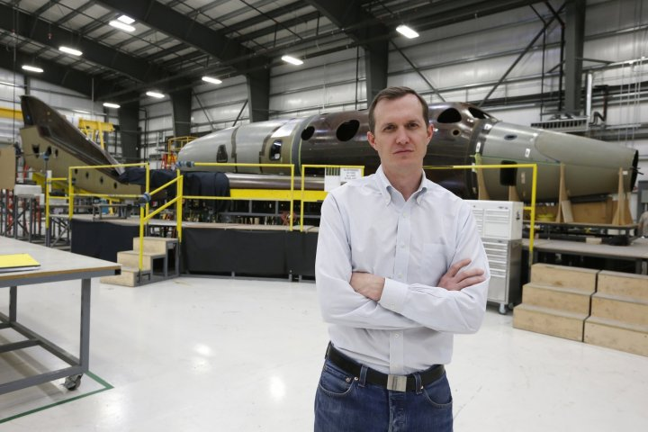 Virgin Galactic's CEO George T. Whitesides stands in front of their new spaceship N202VG, which the company began building 2 and a half years ago, in a hangar at Mojave Air and Space Port in Mojave, California November 4, 2014.
