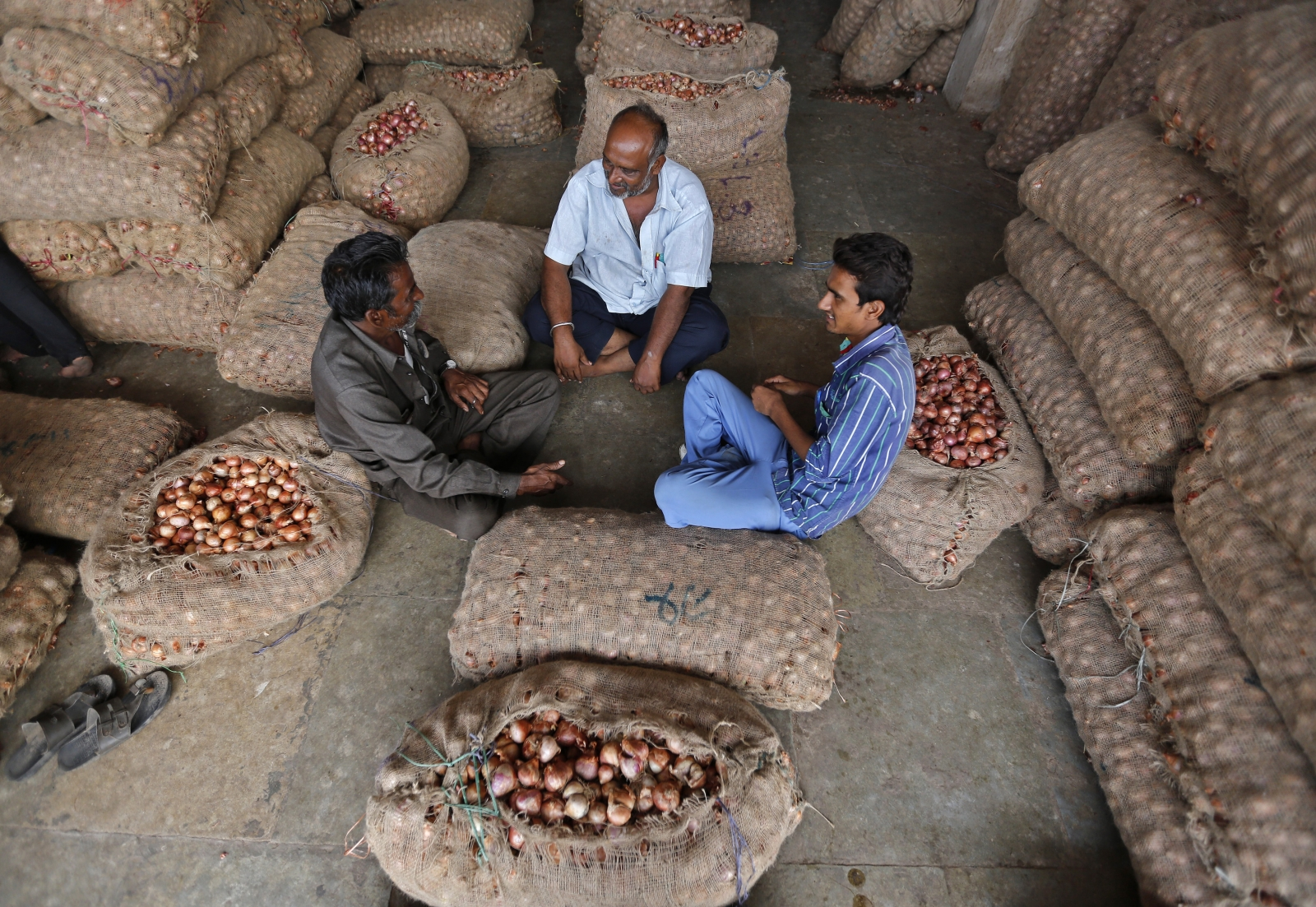 Traders sit amidst stacked sacks, filled with onions and potatoes, at a wholesale vegetable market in the western Indian city of Ahmedabad