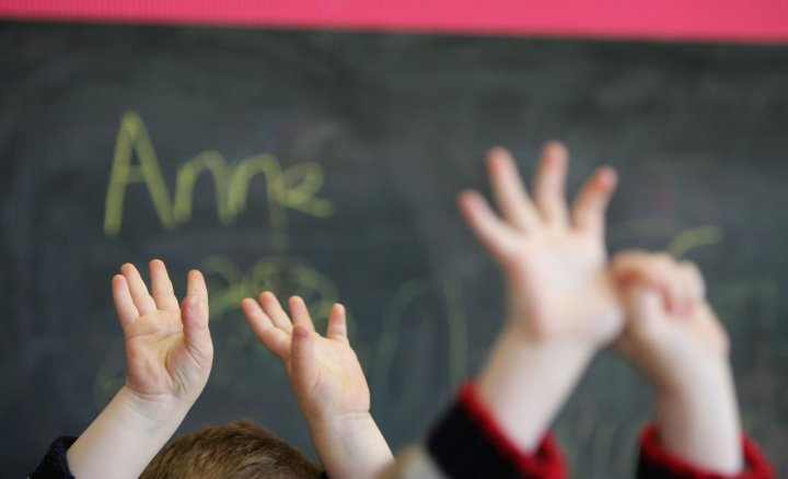 Children in Glasgow raise their hands in class. With their brains malleable, children are able to learn complex skills like language use quickly. (Getty)