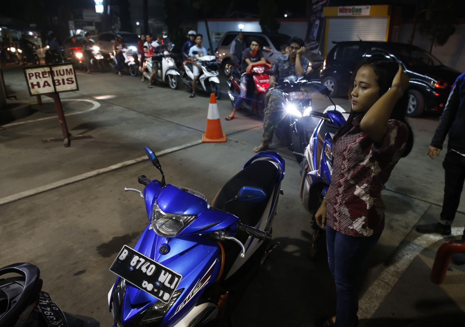 Motorcyclist line up for fuel at a state-owned Pertamina petrol station in Tangerang