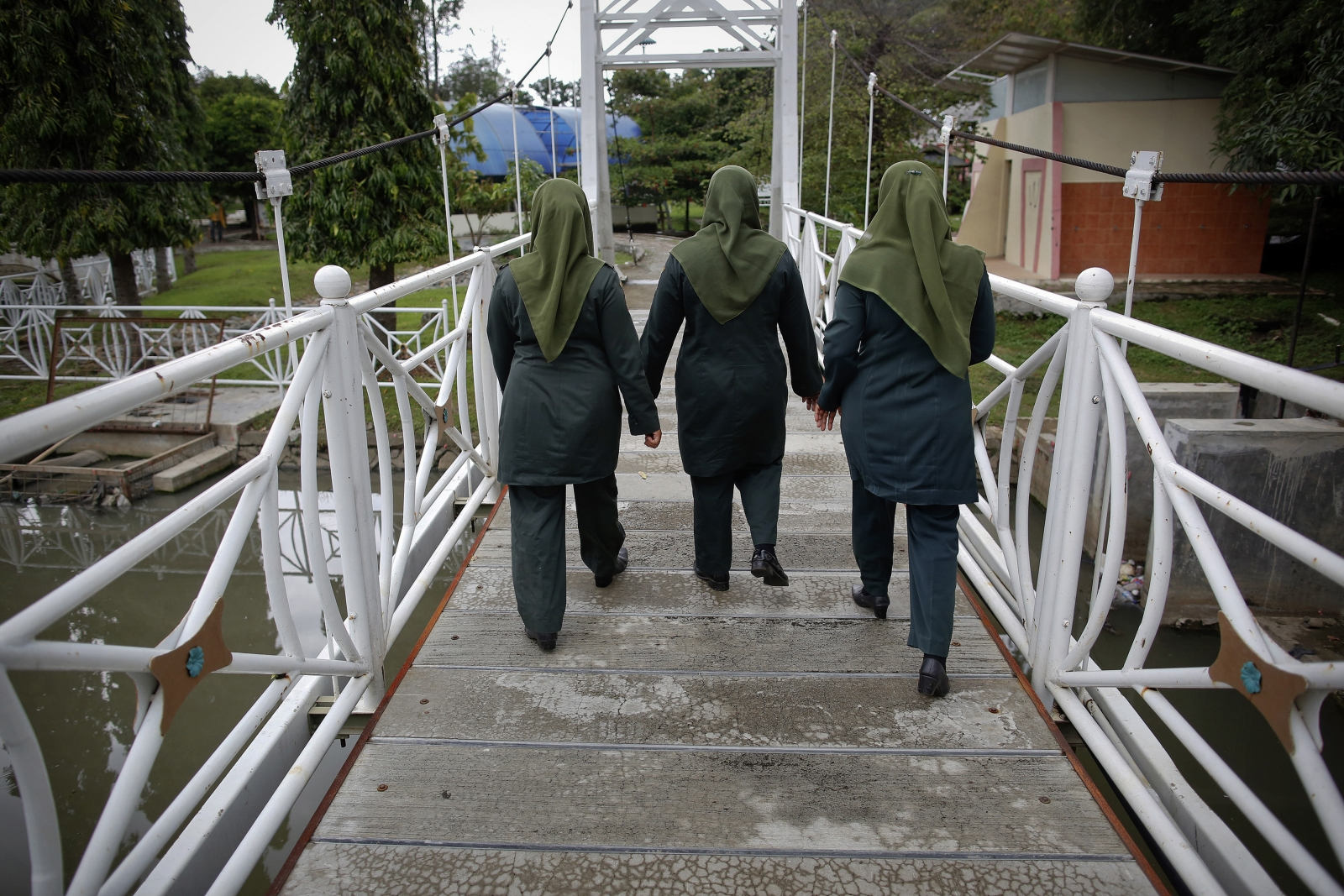 Female members of the sharia police force known as Wilayatul Hisbah (WH) enter a public park as they search for those violating the law during their patrol in Banda Aceh December 6, 2012
