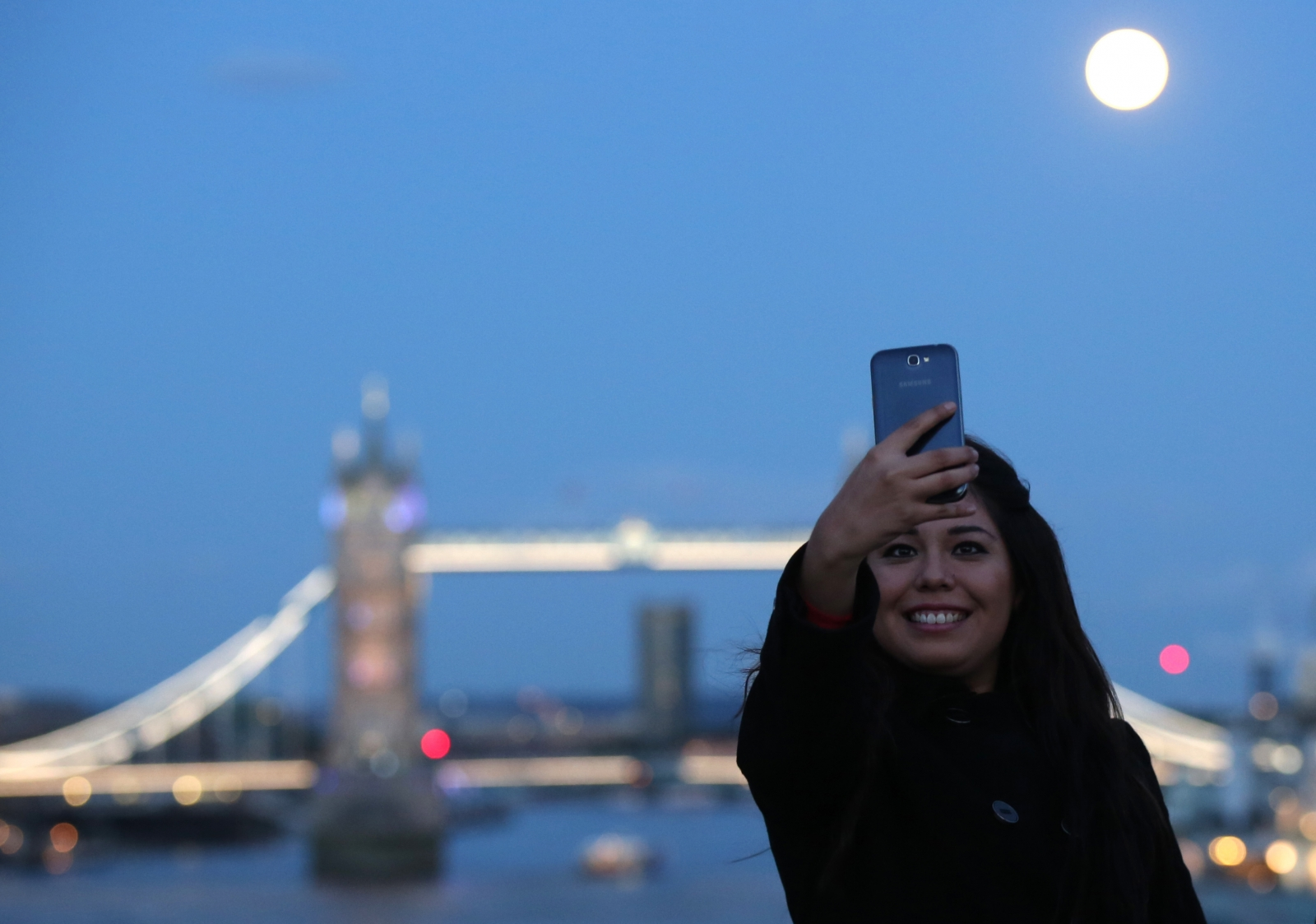 woman takes a selfie as the supermoon rises over Tower Bridge in London
