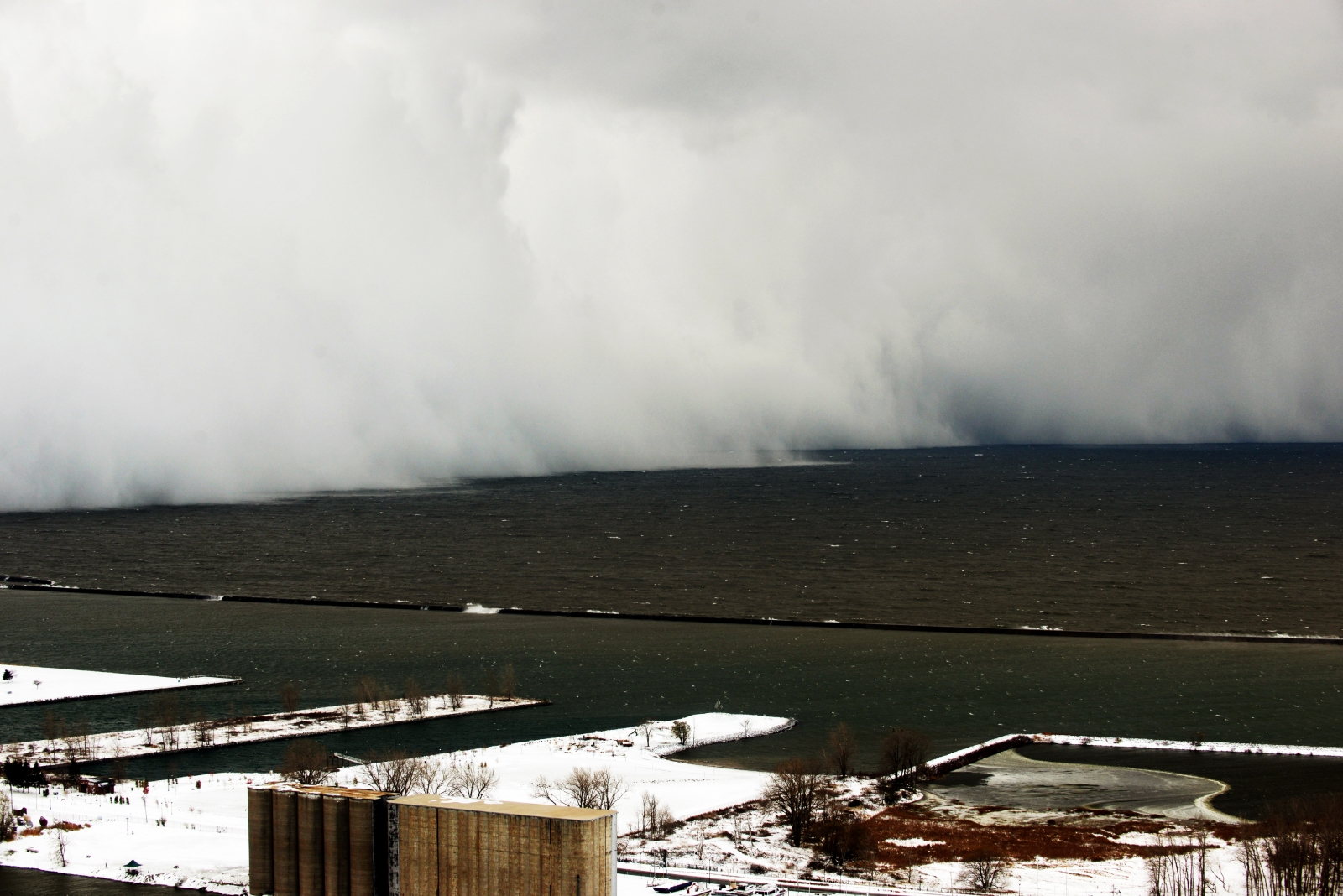 A lake-effect snow storm with freezing temperatures produces a wall of snow travelling over Lake Erie into Buffalo, New York. November 18, 2014. A whirlpool of frigid, dense air known as a
