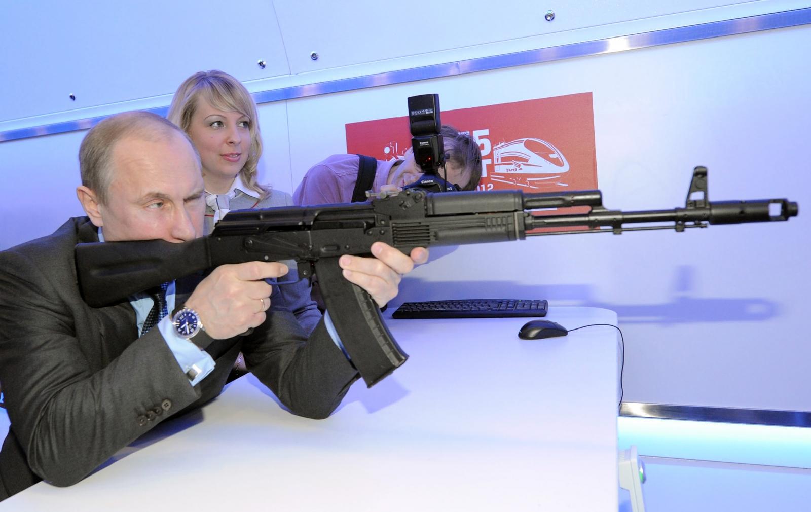 Russian president Vladimir Putin fires a Kalashnikov assault rifle. (Getty)