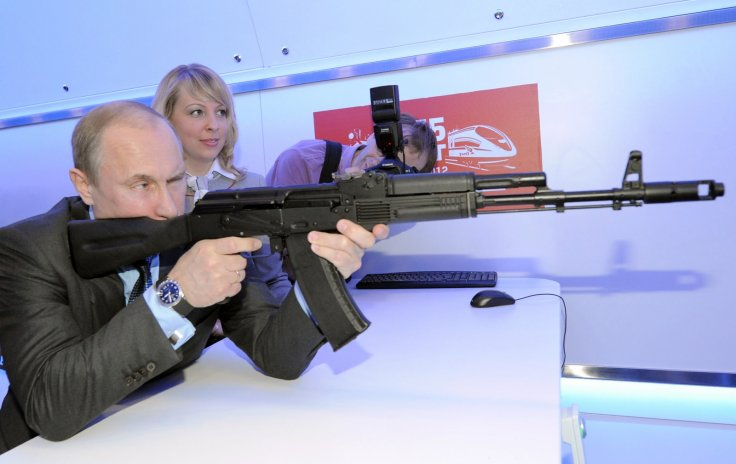 Russian president Vladimir Putin fires a Kalashnikov assault rifle. (Getty)