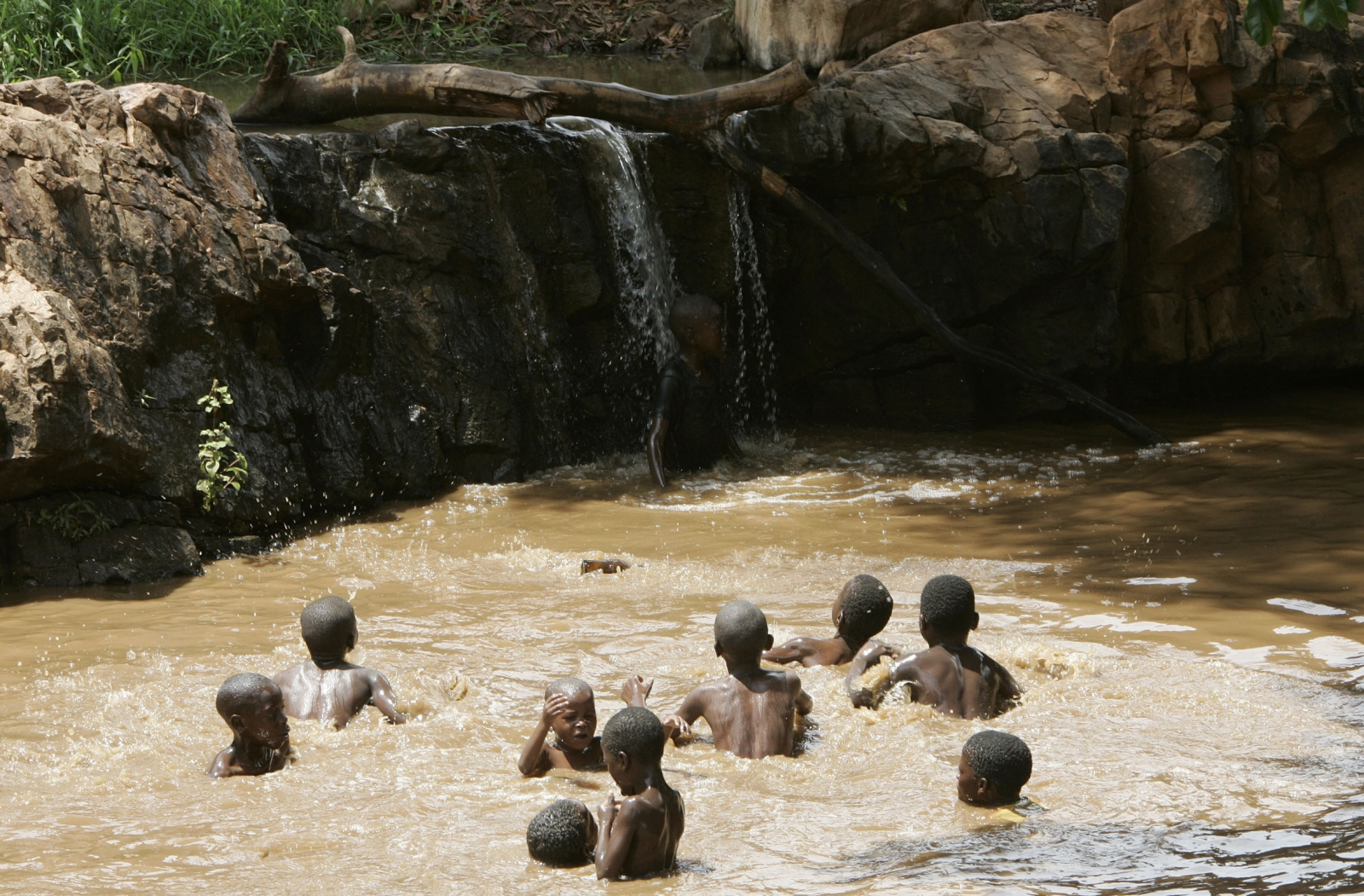 Children enjoy their school holidays by cooling off in muddy water in Tshaulu village in Limpopo province, South Africa, December 28, 2006. REUTERS/Siphiwe Sibeko (SOUTH AFRICA)