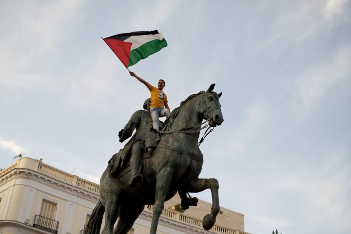 A pro-Palestine protester in Spain climbs a statue of Carlos II in Madrid in July. (Getty)