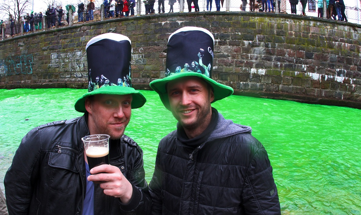 People pose with a Guinness along the river Vilnele as it is colored green to celebrate St Patrick's Day in Lithuania