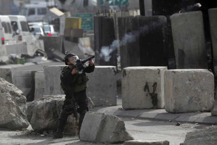 A member of the Israeli security forces clashes with Palestinian protesters