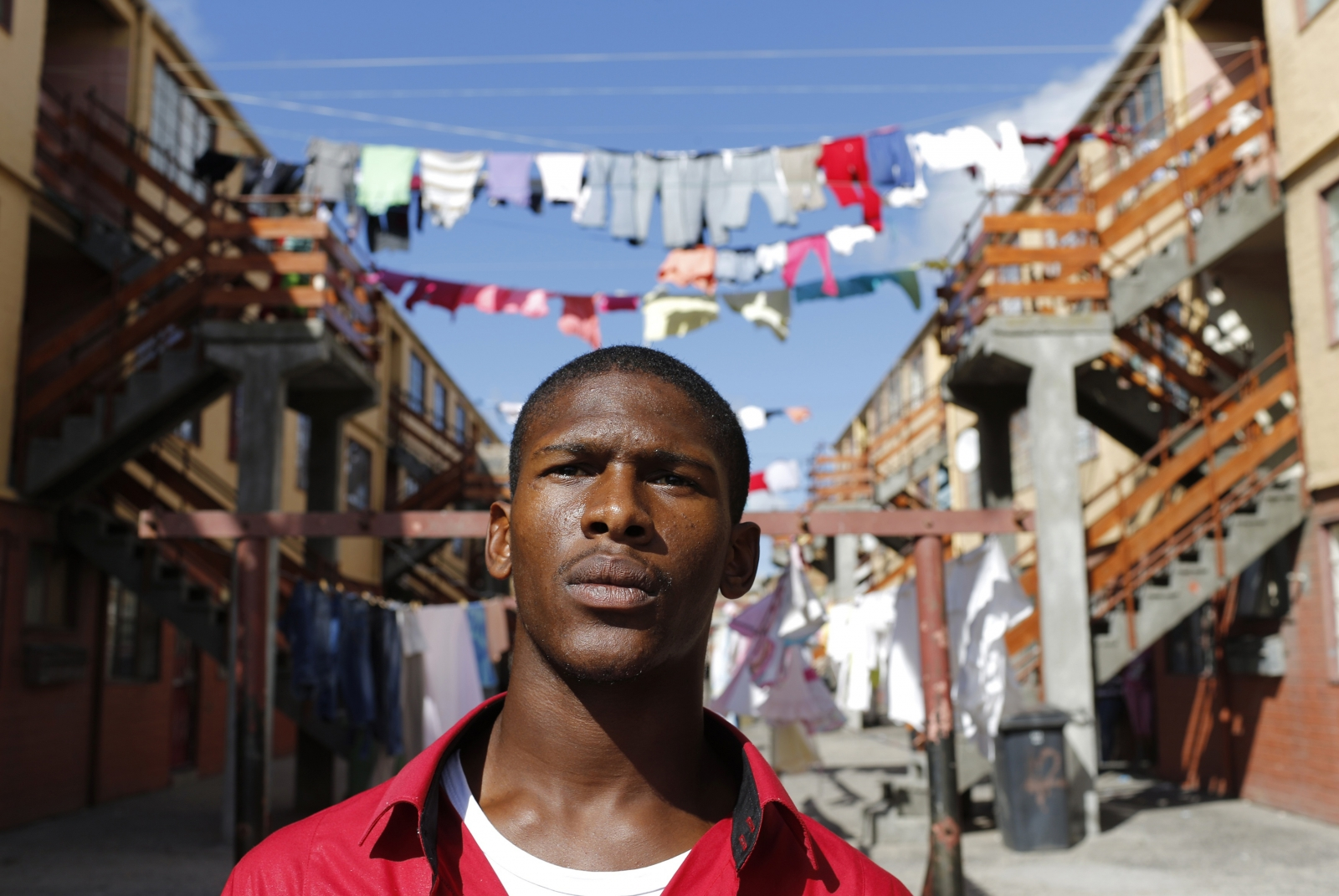 Youth worker Nathaniel Groep, 19, stands in front of flats outside his home in Mannenberg, a gang-ravaged township, in Cape Town April 18, 2014